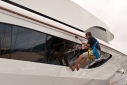 Deckhand cleaning windows of Altitude using a bosun's chair